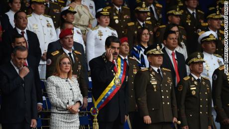 Venezuelan President Nicolas Maduro (C) gestures between his wife Cilia Flores (2-L) and Defence Minister General Vladimir Padrino during a ceremony to celebrate the 81st anniversary of the National Guard in Caracas on August 4, 2018 day in which Venezuela's controversial Constituent Assembly marks its first anniversary. - The Constituent Assembly marks its first anniversary on August 4 as the embodiment of Maduro's entrenchment in power despite an economic crisis that has crippled the country's public services and destroyed its currency. The assembly's very creation last year was largely responsible for four months of street protests that left some 125 people dead. (Photo by Juan BARRETO / AFP)        (Photo credit should read JUAN BARRETO/AFP/Getty Images)
