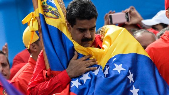 TOPSHOT - Venezuelan President Nicolas Maduro holds a national flag during the closing of the campaign to elect a Constituent Assembly that would rewrite the constitution, in Caracas on July 27, 2017 on the second day of a 48-hour general strike called by the opposition. Venezuela