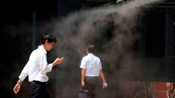 People cool down under a mist in Tokyo on Monday, August 6.