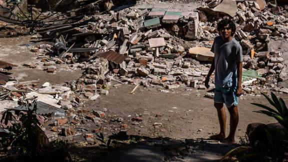 A man stands near the ruins of a collapsed house on Lombok island on Wednesday.