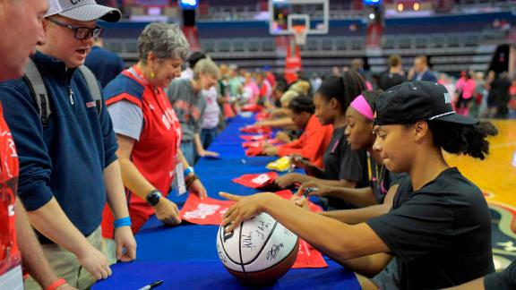 Washington guard Kristi Toliver, right, signs a basketball along with her other teammates at a long table on the floor after their game got canceled between the Washington Mystics and the Las Vegas Aces in Washington DC on Friday.
