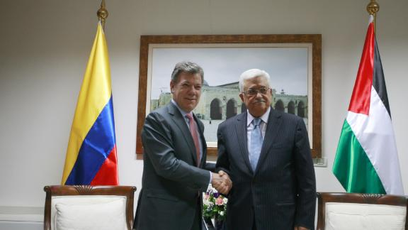 Colombia's former President Juan Manuel Santos (L) poses with Palestinian Authority President Mahmoud Abbas during a 2013 meeting.