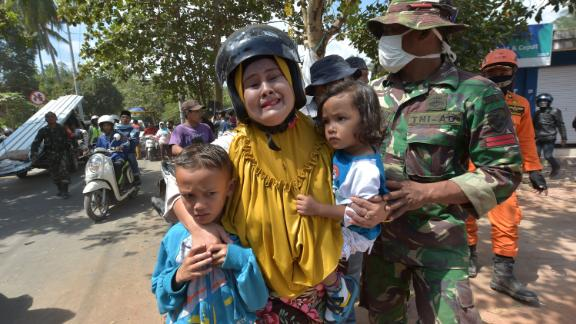 An Indonesian woman cries next to her childern shortly after an aftershock Thursday on Lombok.
