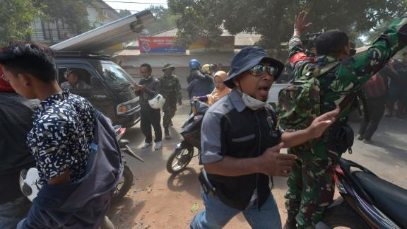 A soldier and an official try to calm people following an aftershock Thursday on Lombok.