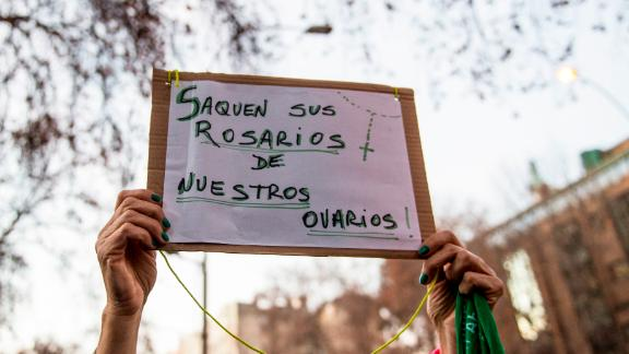 """An activist in favor of legalizing abortion holds a sign reading """"Take your Rosaries from our ovaries"""" during a demonstration outside of Argentina's embassy in Santiago, Chile."""