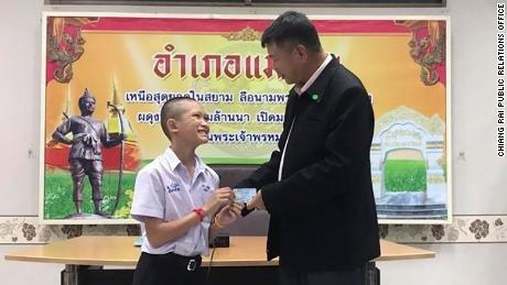 13-year-old Mongkol Boonpiam receives his Thai ID card, denoting Thai citizenship, from the Mae Sai district chief.