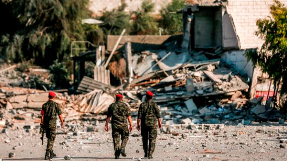 TOPSHOT - Members of Hamas' military police walk through a site that was hit by Israeli air strikes in Gaza City on August 9, 2018. (Photo by MAHMUD HAMS / AFP)        (Photo credit should read MAHMUD HAMS/AFP/Getty Images)