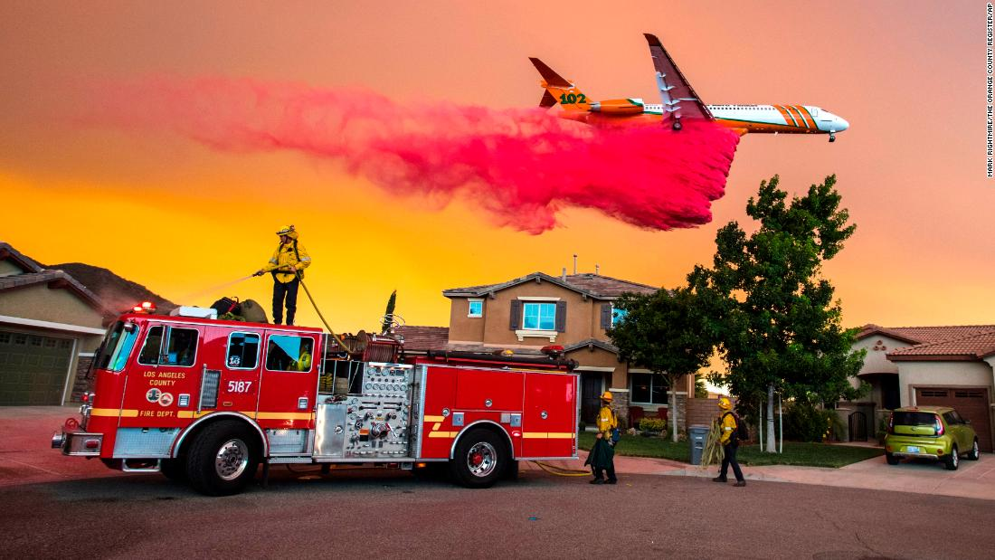 "A plane drops fire retardant behind homes as the Holy Fire burns in Lake Elsinore, California, on Wednesday, August 8. More than 14,000 firefighters <a href=""http://www.cnn.com/2018/07/27/us/gallery/california-wildfires/index.html"" target=""_blank"">are battling catastrophic wildfires</a> that continue to ravage parts of the state."