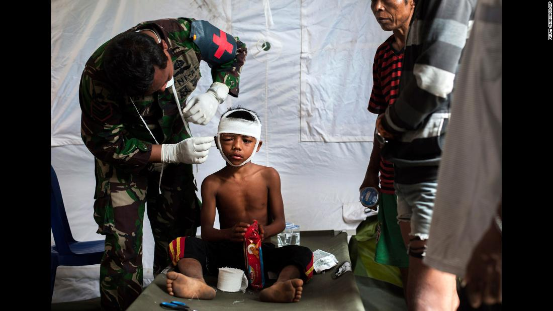 "A military paramedic tends to a boy who suffered a head injury during an earthquake that happened Sunday, August 5, on the Indonesian island of Lombok. The death toll from <a href=""https://www.cnn.com/2018/08/08/asia/indonesia-earthquake-intl/index.html"" target=""_blank"">the 6.9 magnitude quake</a> has risen to 347, and it is expected to be higher once all the bodies can be counted, according to the state-run Antara news agency."