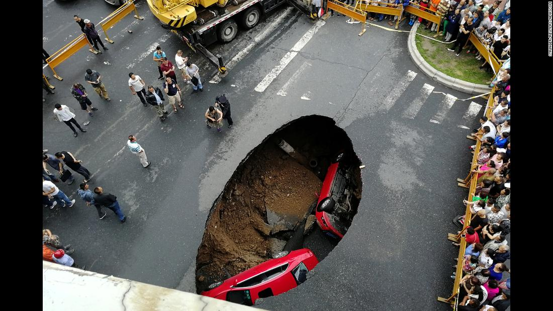"People gather near the scene where two vehicles fell into a sinkhole in Harbin, China, on Saturday, August 4. No one was hurt, <a href=""https://www.scmp.com/news/china/society/article/2158328/road-sinkhole-swallows-two-cars-northern-china"" target=""_blank"">according to the South China Morning Post.</a>"