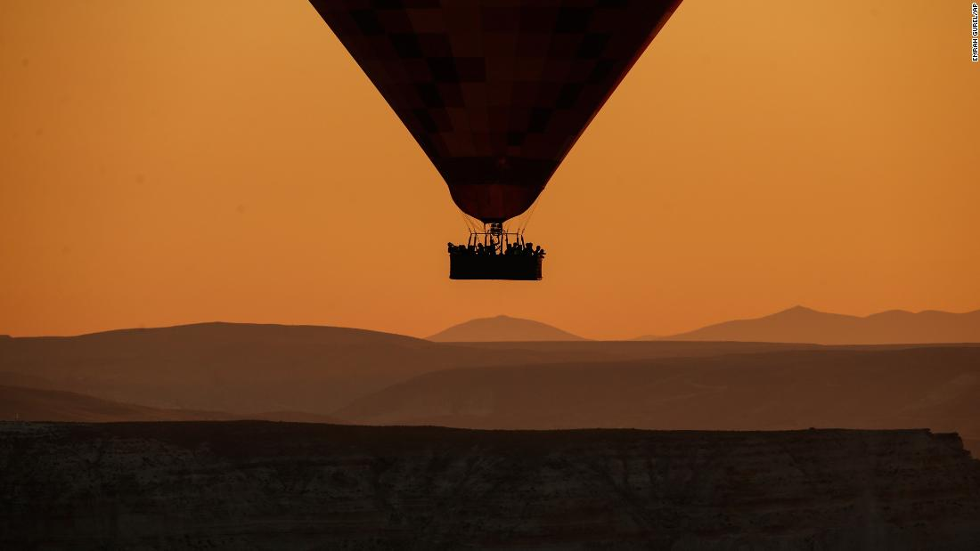A hot-air balloon carries tourists at sunrise Tuesday, August 7, in Cappadocia, Turkey. Cappadocia is a popular spot for hot-air balloons, which slowly drift above cone-shaped rock formations and rippled ravines to provide breathtaking views of the region.