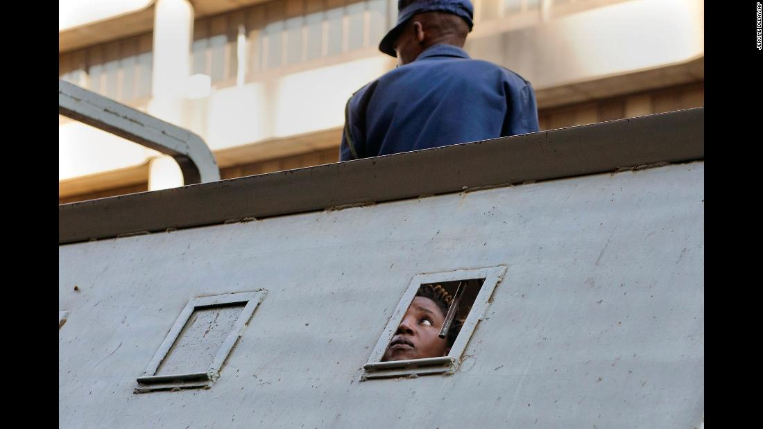 "A supporter of Zimbabwe's main opposition party, the Movement for Democratic Change, looks out from a police vehicle after being detained outside MDC's headquarters in Harare on Thursday, August 2. Harare <a href=""https://www.cnn.com/2018/08/02/africa/zimbabwe-election-violence-intl/index.html"" target=""_blank"">resembled a ghost town</a> on that day, less than 24 hours after security forces and opposition protesters clashed over the results of the country's elections."
