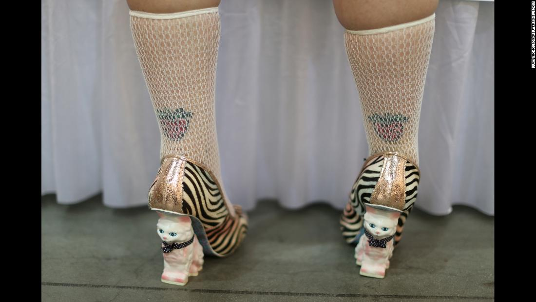 A woman with cat shoes stands at a booth at the CatCon cat convention in Pasadena, California, on Sunday, August 5.