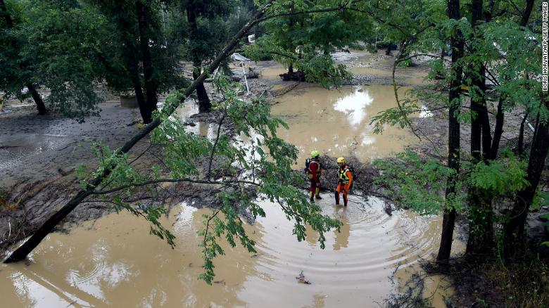Rescuers Stand In A Flooded Area Near Saint Julien De Peyrolas Southern