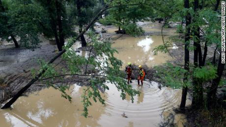 Rescuers stand in a flooded area near Saint-Julien-de-Peyrolas, southern France.