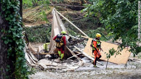 Rescuers walk past a damaged tent in Saint-Julien-de-Peyrolas.