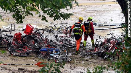 Rescuers walk past damaged bicycles in a flooded camping area on August 9 in Saint-Julien-de-Peyrolas in southern France.