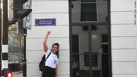 Activist Naomi Zaloumis pointing to one of the new signs