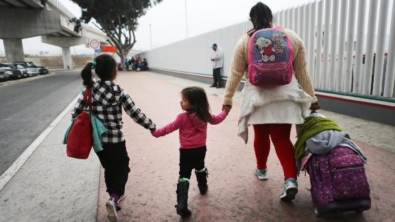 A migrant woman walks with her two daughters on their way to cross the port of entry into the U. for their asylum hearing on June 21, 2018, in Tijuana, Mexico. (Photo by Mario Tama/Getty Images)