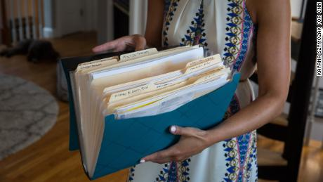 """Kate Weissman displays her """"cancer folder"""" containing the paperwork involved in her  treatment and battle with her insurance company."""