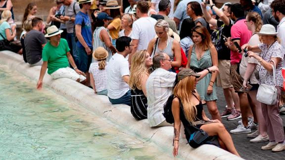 Tourists cool themselves in the water of the Trevi Fountain in central Rome on July 14, 2018, as Italy is experiencing its first Summer heat wave with temperatures approaching 40 degrees Celsius. (Photo by Andreas SOLARO / AFP)        (Photo credit should read ANDREAS SOLARO/AFP/Getty Images)