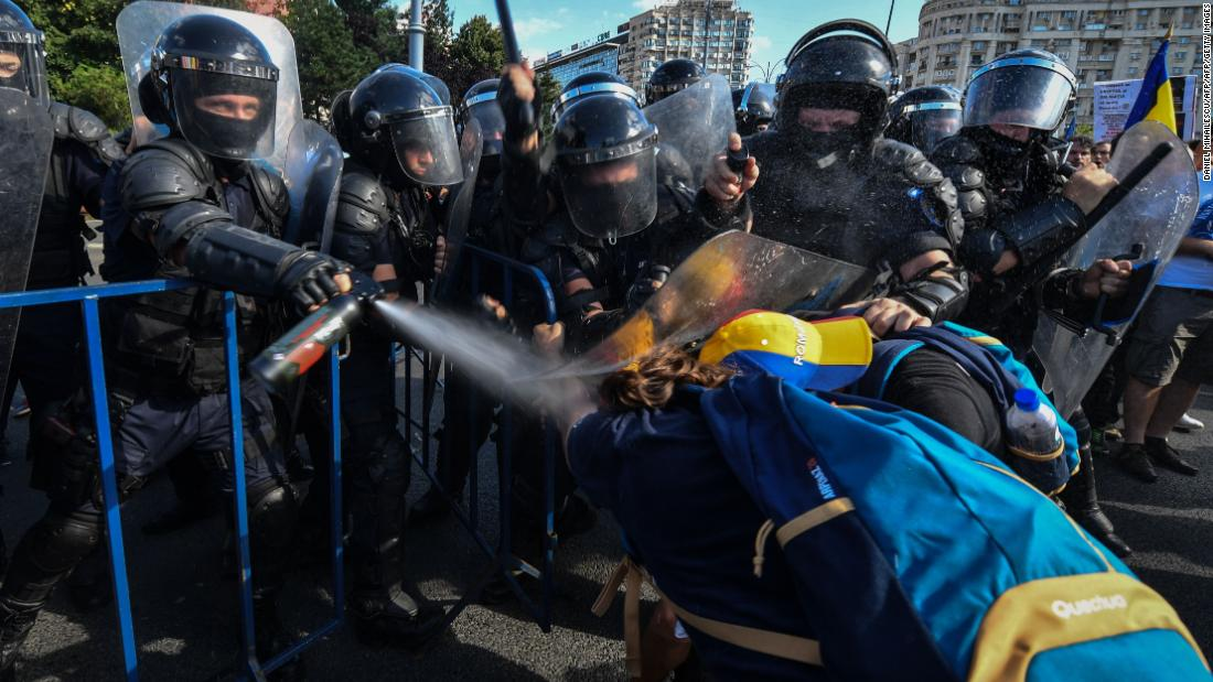 Anti-government protesters and police clash in Romania