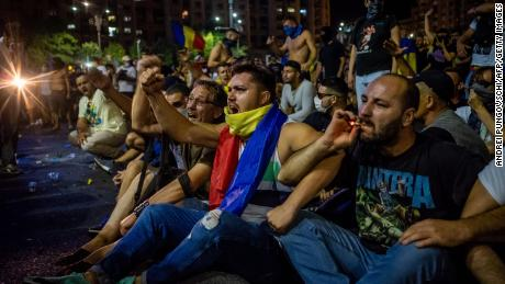 Romanians take part in a demonstration in front of the government headquarters in Bucharest on Friday.
