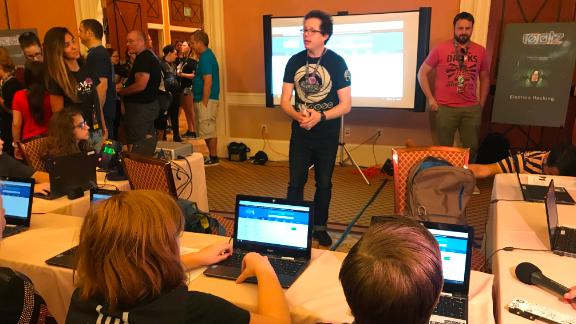 Children prepare to hack mock versions of state election websites at DEF CON on Friday. (Photo by Donie O