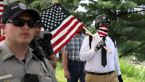Police escort white supremacists to a metro station before the rally on August 12, 2018.