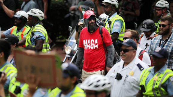 """VIENNA, VA - AUGUST 12:  DC Metro Police form a protective phalanx around participants in the white supremacist Unite the Right rally as they march to White House August 12, 2018 in Washington, DC. Thousands of protesters are expected to demonstrate against the """"white civil rights"""" rally in Washington, which was planned by the organizer of last yearÕs deadly rally in Charlottesville, Virginia.  (Photo by Chip Somodevilla/Getty Images)"""