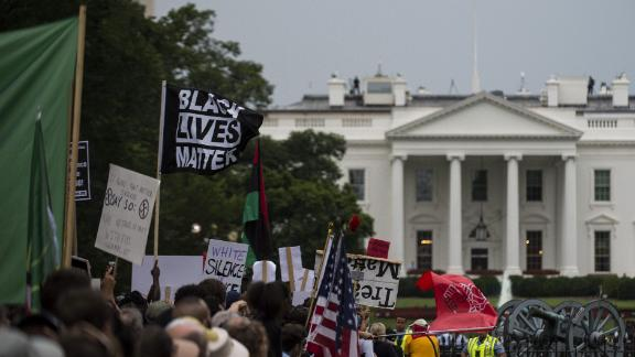 Demonstrators opposed to a far-right rally hold posters and banners in front of the White House August 12, 2018 in Washington, DC, one year after the deadly violence at a similar protest in Charlottesville, Virginia. - Last year's protests in Charlottesville, Virginia, that left one person dead and dozens injured, saw hundreds of neo-Nazi sympathizers, accompanied by rifle-carrying men, yelling white nationalist slogans and wielding flaming torches in scenes eerily reminiscent of racist rallies held in America's South before the Civil Rights movement. (Photo by Eric BARADAT / AFP)        (Photo credit should read ERIC BARADAT/AFP/Getty Images)
