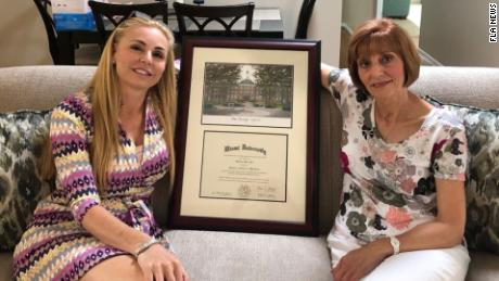 Melissa Howard holds a framed diploma, but Miami University suggests it's not real.