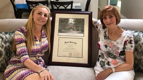 Melissa Howard, left, holds a framed diploma, but Miami University suggests it's not real.
