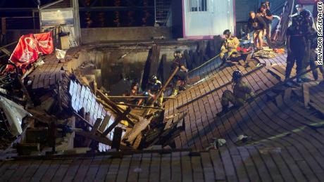 Firefighters search for victims after a wooden platform collapsed during a concert in Vigo late Sunday.