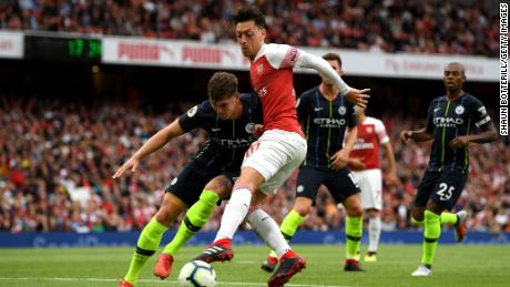 "Arsenal's Mesut Ozil wears the ""Visit Rwanda"" logo on the sleeve during the team's season opener."