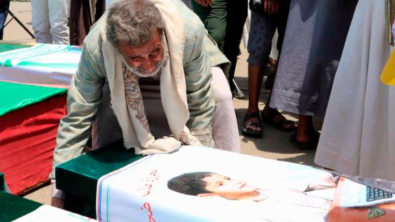 A man mourns over the casket of one of the children killed in the strike.
