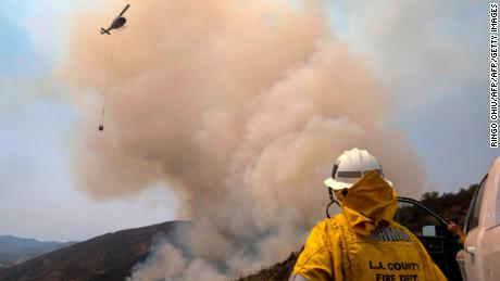 A firefighter watches as a helicopter drops water to combat the Holy Fire in Lake Elsinore, California in August.