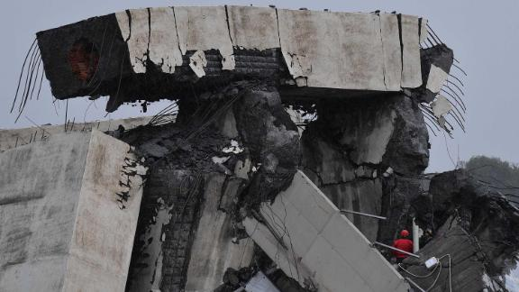 A chunk of the collapsed bridge teeters atop the rubble.