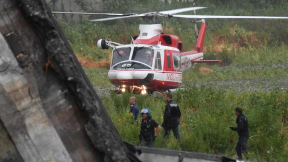 A rescue helicopter lands near the site of the collapse.