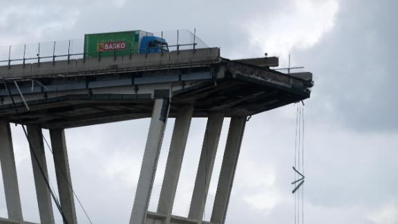 """TOPSHOT - A picture taken on August 14, 2018 in Genoa shows a view of the Ponte Morandi motorway bridge, after one of its section collapsed injuring several people. - Rescuers scouring through the wreckage after part of a viaduct of the A10 freeway collapsed said there were """"tens of victims"""", while images from the scene showed an entire carriageway plunged on to railway lines below. (Photo by ANDREA LEONI / AFP)        (Photo credit should read ANDREA LEONI/AFP/Getty Images)"""