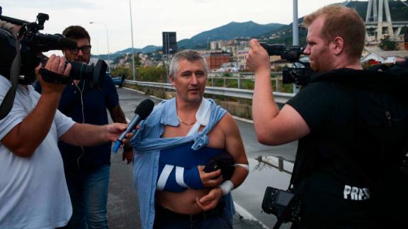 An injured man speaks to reporters near the bridge.