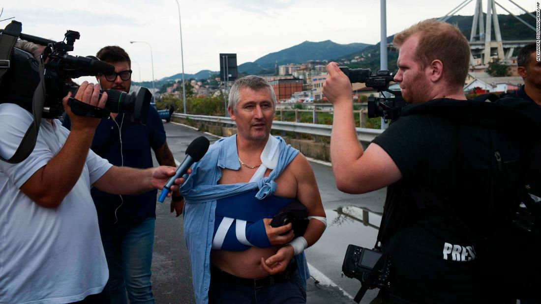 An injured man speaks to reporters near the bridge.