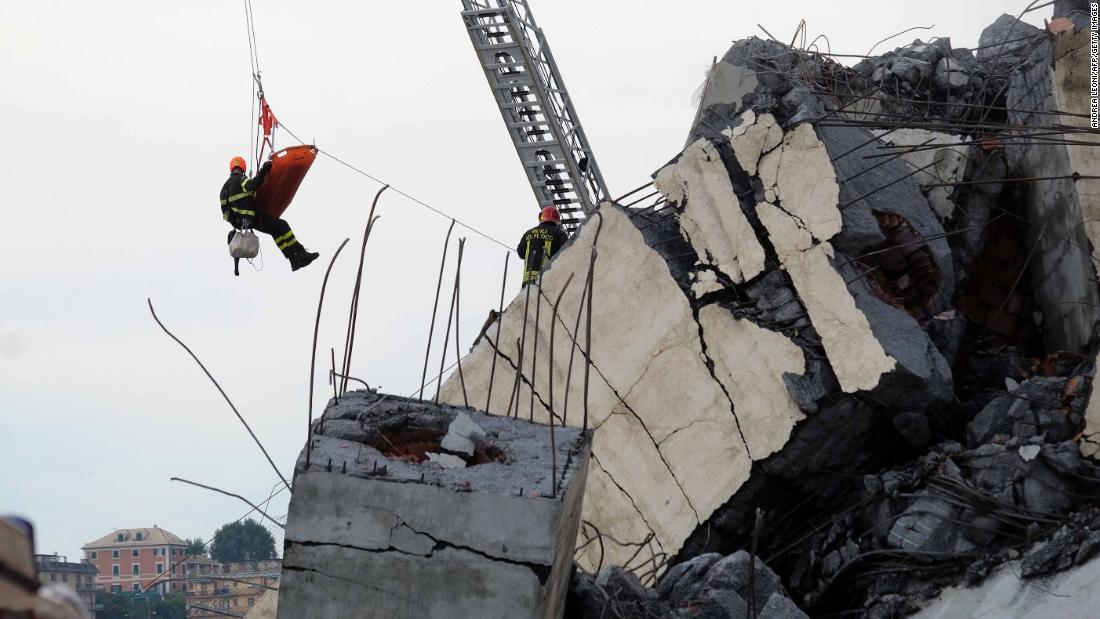 A rescuer and a stretcher are lifted above the wreckage.
