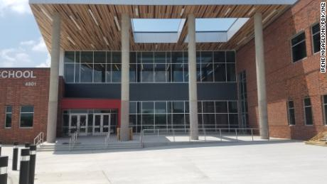 The entrance to this middle school, designed by PBK/IN2 Architecture, includes large glass windows, protective poles and an entrance clearly outlined in red.