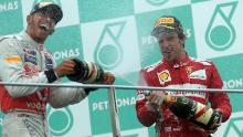 Ferrari driver Fernando Alonso of Spain (R) and McLaren-Mercedes driver Lewis Hamilton (L) of Britain celebrate on the podium with champagne after Formula One's Malaysian Grand Prix in 2012.