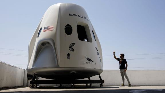 An attendee takes pictures of a mock up of the Crew Dragon spacecraft ahead of the NASA Commercial Crew Program (CCP) astronaut visit at the Space Exploration Technologies Corp. (SpaceX) headquarters in Hawthorne, California, U.S., on Monday, Aug. 13, 2018. Astronauts on SpaceX's Crew Dragon will be the first to fly on an American-made, commercial spacecraft to and from the International Space Station on their mission scheduled for April 2019. Photographer: Patrick T. Fallon/Bloomberg via Getty Images