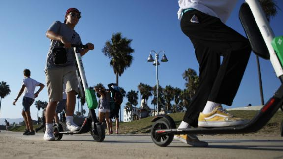 People ride Lime scooters along Venice Beach on August 13 in Los Angeles, California.