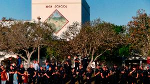 TOPSHOT - Marjory Stoneman Douglas High School staff, teachers and students return to school greeted by police and well wishers in Parkland, Florida on February 28, 2018. Students grieving for slain classmates prepared for an emotional return Wednesday to their Florida high school, where a mass shooting shocked the nation and led teen survivors to spur a growing movement to tighten America's gun laws. The community of Parkland, Florida, where residents were plunged into tragedy two weeks ago, steeled itself for the resumption of classes at Marjory Stoneman Douglas High School, where nearby flower-draped memorials and 17 white crosses pay tribute to the 14 students and three staff members who were murdered by a former student. / AFP PHOTO / RHONA WISE (Photo credit should read RHONA WISE/AFP/Getty Images)