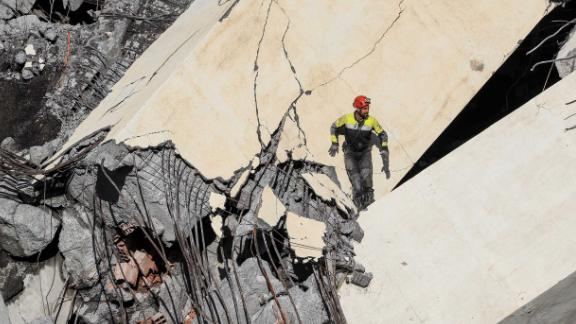 A rescuer climbs through the rubble of the bridge in search of victims and survivors.