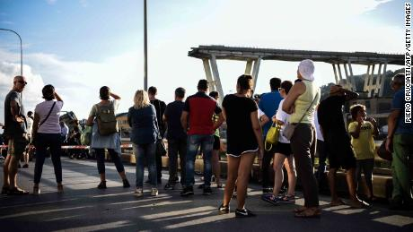 People stand looking at the Morandi motorway bridge after a section collapsed in the northern city of Genoa on Tuesday.